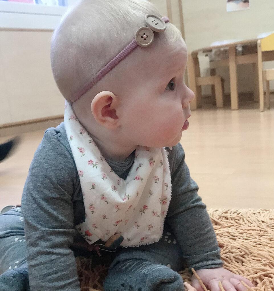 bebé sentado en alfombra en una clase de guaredría