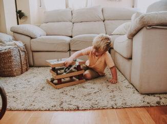 niño jugando con un párking de cartón